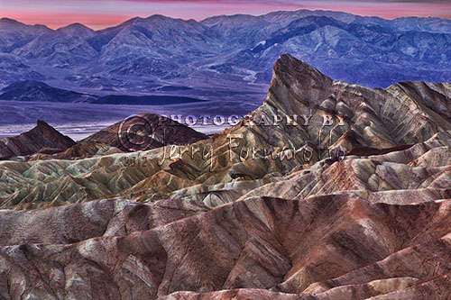 This photo was taken moments before sunrise from Zabriskie Piont Lookout, Death Valley National Park. The foreground of this scene shows the Badlands formations, Manly Beacon, Death Valley and the Panamint Range in the distance. The photo was captured with a Canon 1D Mark IV and a Canon 24-70mm L lens set to 70mm.