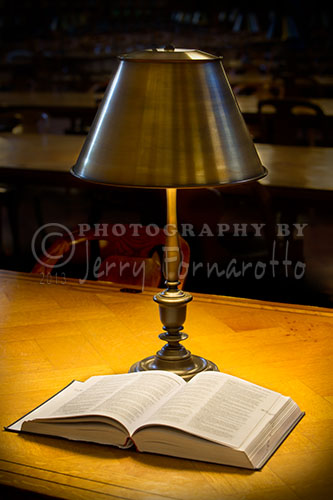 A reading lamp and book on one of the long oak tables in the Rose Main Raeding Room. The Rose Room is located in the New York Library main branch on Fifth Avenue, NYC.
