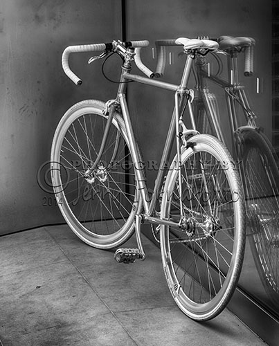 A black and white photo of a sleek looking bicycle in front of the Apple Store, Charleston, SC.