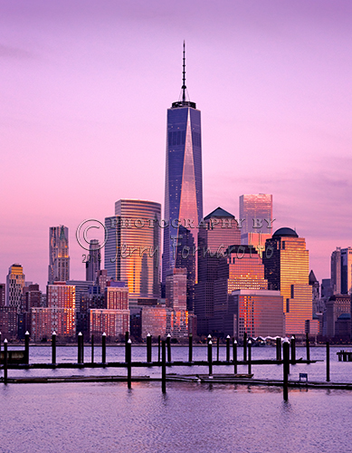This is photo of Lower Manhattan, NYC, was taken from Jersey City, New Jersey at dusk. The Freedom Tower is in the center. To the left of the tower is the Woolworth Building. Behind the Woolworth Building is the Beekman Tower. Right of the Freedom Tower is the World Financial Center.