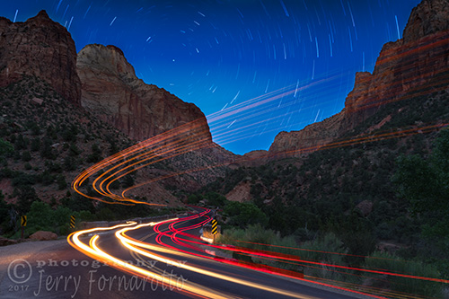 A long exposure photo of car light trails traveling through Zion National Park, Utah.