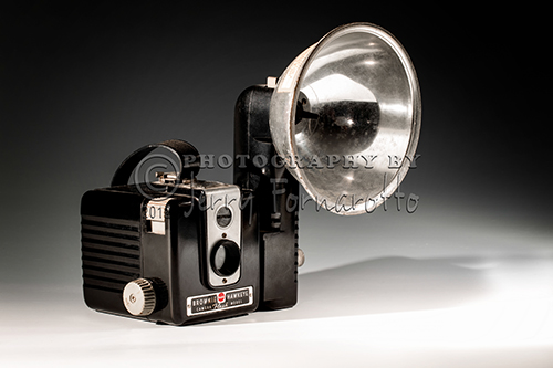 A still life photo of an old Brownie Hawkeye camera with flash. Brownie is the name of a long-running popular series of simple and inexpensive cameras made by Eastman Kodak. The Brownie popularized low-cost photography and introduced the concept of the snapshot.