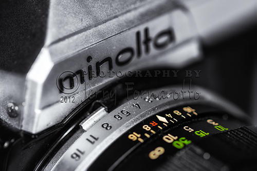 "A closeup photo of a Minolta XG7. The first model of this series to be introduced in 1977. Minolta is best known for making the first autofocus 35mm SLR camera. Minolta is an acronym for ""Mechanism, Instruments, Optics, and Lenses by Tashima."""