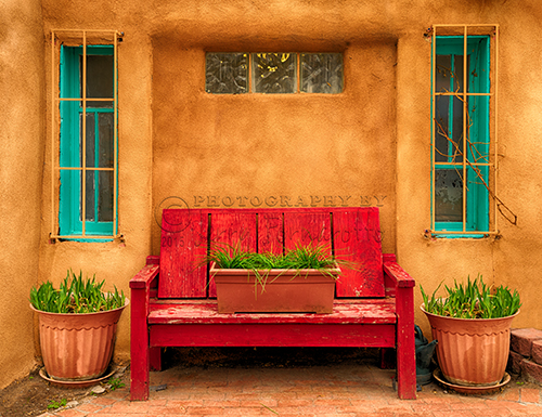 "A bright red bench in ""Old Town"" Albuquerque, New Mexico."