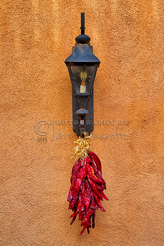 A bunch of dried chili peppers hanging from a lamp.