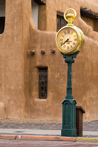 Santa Fe Square Clock stand in front of the New Mexico Museum of Art at the corner of Lincoln and W. Palace Aves.