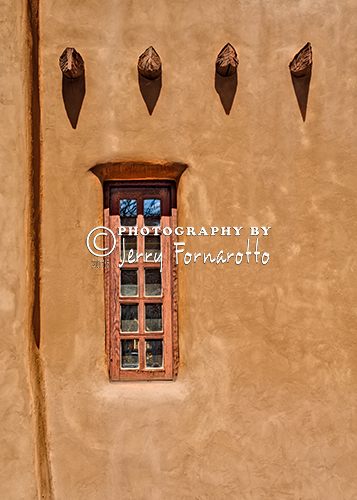 An adobe window and vigas.
