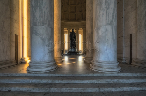 The interior of the Jefferson Memorial illuminated with golden light.