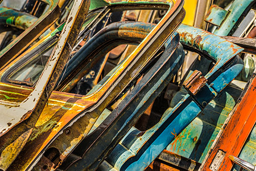 A stack of old rusty car doors found in a car junk yard.