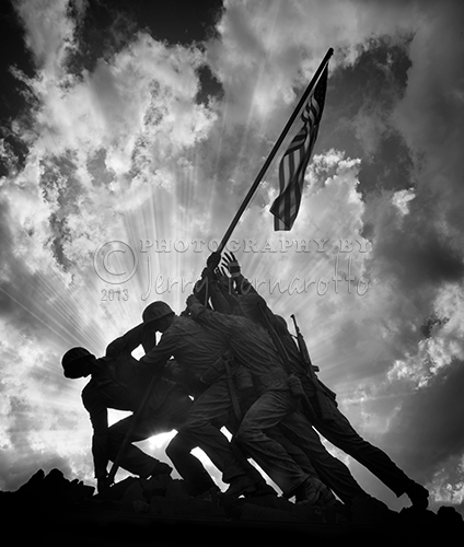 A sunset black and white photo of the Marine Corps War Memorial. This memorial is sometimes called the Iwo Jima Memorial.