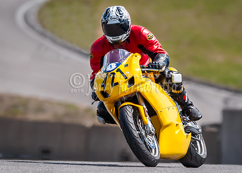A yellow Ducati Super motorcycle racing.