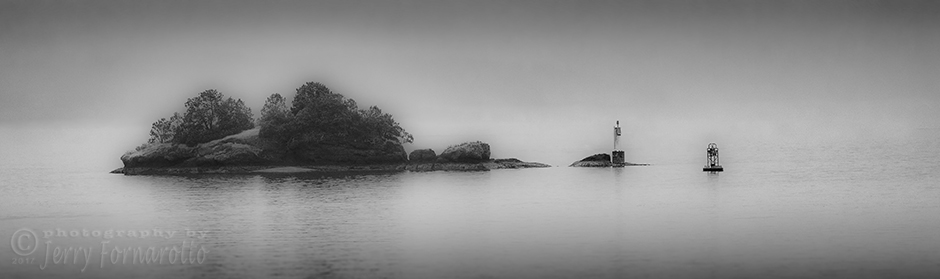 A small island in the fog of the coast of Victoria Island, B.C., Canada.
