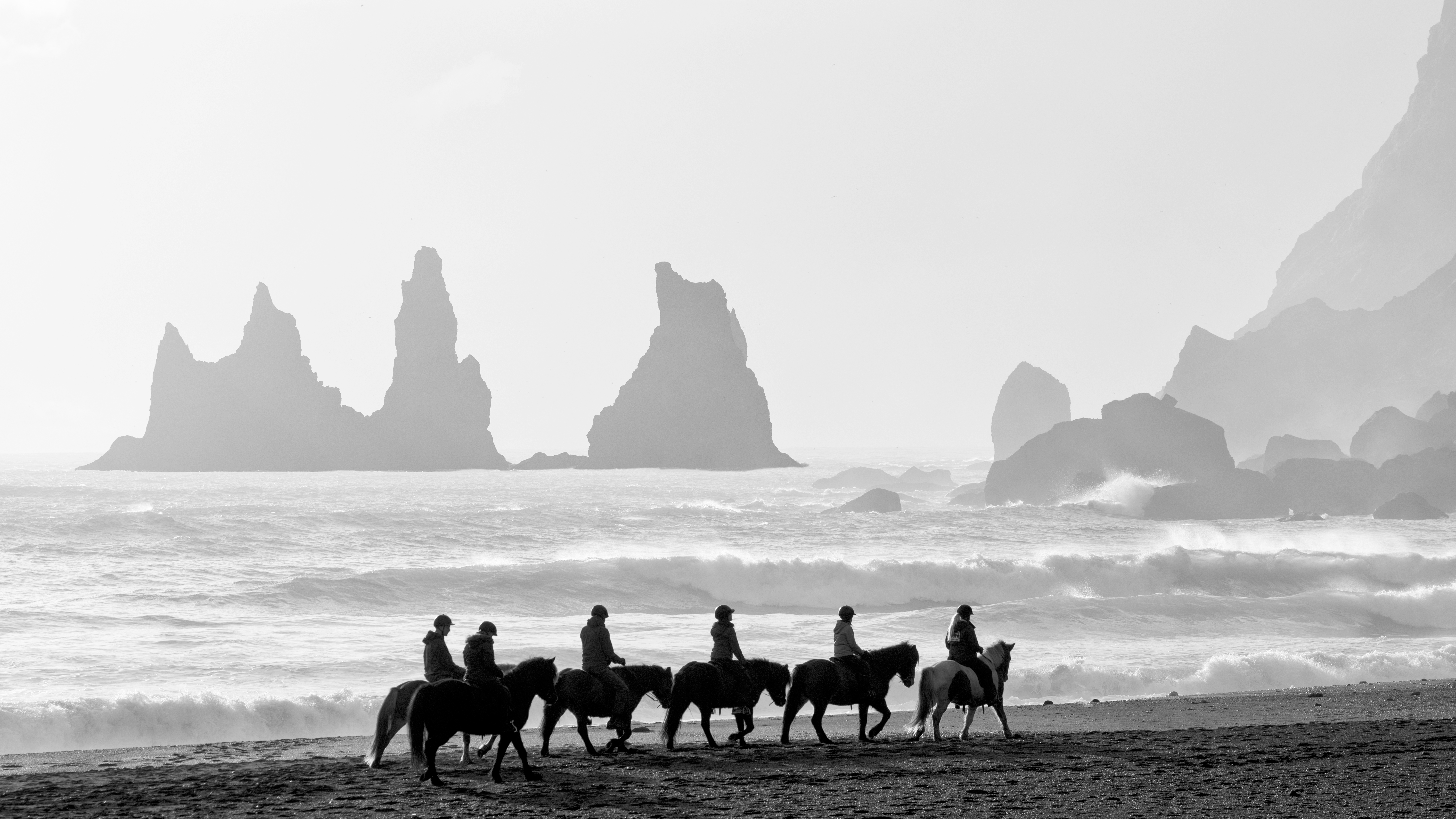 A group of riders at Reynisfjara Beach. This beach is a beautiful black sand beach under Reynisfjall mountain, not far from the city of Vik, Iceland.